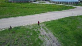 Abejón del vuelo que sigue una opinión aérea de la muchacha del campo, vídeo de la opinión superior 4K UHD del abejón almacen de video