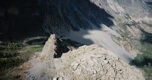 Abejón que critica a la derecha sobre canto grande de la montaña rocosa para revelar el camino soleado asombroso del acantilado e almacen de metraje de vídeo