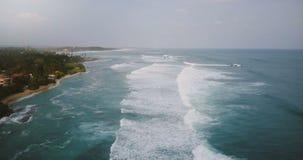 Abejón que desciende sobre vista panorámica increíble de la playa nublada tropical exótica, ondas que lavan la orilla y hacer esp almacen de metraje de vídeo