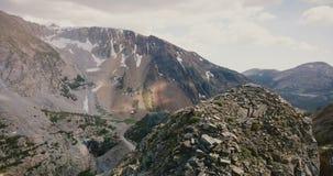 Abejón que gira sobre el pico cubierto de piedra que revela cantos cinemáticos extensos de la roca de la montaña en el parque nac metrajes