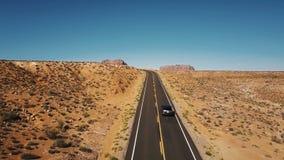 Abejón que sube para arriba sobre el coche que se mueve a lo largo del camino vacío del desierto para revelar horizonte asombroso almacen de video