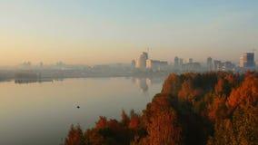 Abejón que sube sobre los árboles del otoño que revelan el lago inmóvil épico de la puesta del sol, horizonte distante grande de  almacen de video