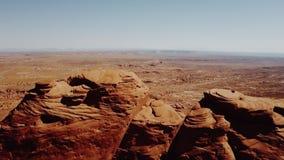 Abejón que sube sobre los acantilados masivos en valle de los monumentos en Arizona que revela espacios abiertos extensos sin fin metrajes