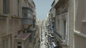 Abejón que vuela adelante en la calle vieja hermosa estrecha, La Valeta, Malta Viejo, ventanas del vintage, balcones - 4K almacen de metraje de vídeo