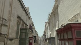 Abejón que vuela adelante la elevación para arriba en la calle vieja hermosa estrecha, La Valeta, Malta El coche blanco elimina B almacen de video