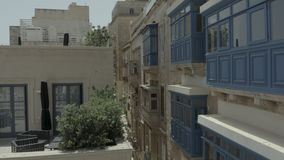 Abejón que vuela adelante a través de la calle vieja hermosa, La Valeta, Malta Viejo, ventanas del vintage, balcones - 4K almacen de video