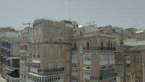 Abejón que vuela para arriba a través de la calle vieja hermosa, La Valeta, Malta Viejo, ventanas del vintage, balcones - 4K almacen de video