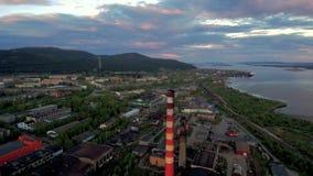 Abejón que vuela sobre una ciudad soviética septentrional típica Fábricas, tubos, manzanas y colinas en el fondo metrajes