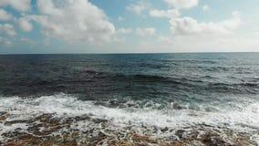 Abejón tirado de las olas oceánicas que golpean la playa rocosa Vista aérea de las ondas del mar que salpican contra la playa metrajes