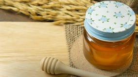 Abeja de la miel en la botella de cristal en la tabla de madera Fotos de archivo