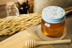 Abeja de la miel en la botella de cristal en la tabla de madera Fotografía de archivo