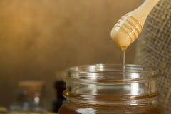 Abeja de la miel en la botella de cristal en la tabla de madera Imagen de archivo libre de regalías