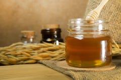 Abeja de la miel en la botella de cristal en la tabla de madera Imagen de archivo