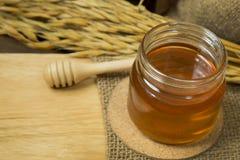 Abeja de la miel en la botella de cristal en la tabla de madera Fotos de archivo libres de regalías