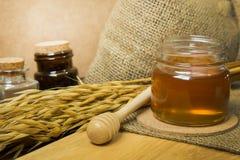 Abeja de la miel en la botella de cristal en la tabla de madera Imágenes de archivo libres de regalías