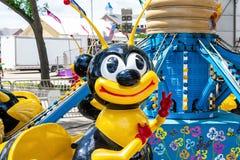 Abeja feliz que destella un signo de la paz en paseo del carnaval Foto de archivo