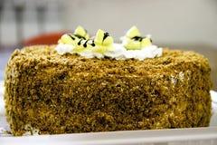 Abeja poner crema en una torta de chocolate Fotografía de archivo libre de regalías