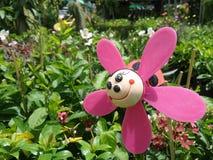 Abeja rosada sonriente en jardín de flores Foto de archivo libre de regalías
