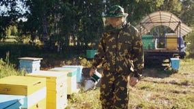 Abejas que fuman del hombre joven del apicultor lejos de la colmena en colmenar Imágenes de archivo libres de regalías