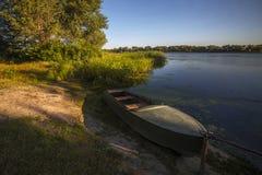 Am Abend ein Boot auf dem Ufer von einem glatten Fluss Stockfotos