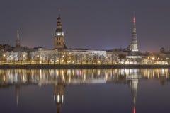 Abendansicht über den Damm des Daugava-Flusses und die spiers von Kirchen in Riga lizenzfreie stockfotos