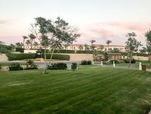 Abendansicht des Grüns des Rasens und des arabischen arabischen islamischen weißen Gebäudes Häuschen vor dem hintergrund des trop stockfotografie