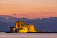 Abendansicht von Bourtzi-Festung mit Bergen im Hintergrund in Nafplio lizenzfreies stockfoto