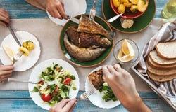 Abendessen mit gebratenen Fischen, Kartoffeln und frischem Salat Lizenzfreies Stockbild