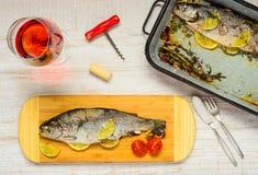 Abendessen mit gekochten Fischen und Rose Wine lizenzfreie stockfotos