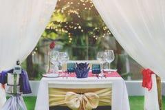 Abendessen-Satz die Tabelle mit romantischer Art des Weins und der Rose nahe dem Pool Stockfotos