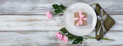 Abendesseneinstellung mit rosa Rosen und Geschenk auf rustikalem weißem Holz Stockfotos