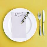 Abendessenmenü für eine Hochzeit oder ein Luxusabendessen Gedeck von oben Elegante leere Platte, Tischbesteck und Blumen Lizenzfreie Stockfotos