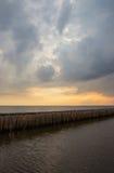 Abendhimmel und Reihen von Bambusstöcken im Meer nahe Matchanu-Schrein, Phanthai Norasing, Bezirk Mueang Samut Sakhon, Samut Sakh Lizenzfreie Stockfotografie