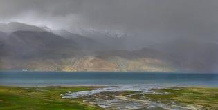 Abendnebel auf dem Hochgebirge des Sees: graue Wolken steigen zu den Bergen, verstecken sie, die letzten Strahlen des Sonne illum Stockbild
