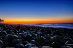 Abendrot über Strand-Felsen Stockbilder