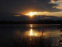 Abendsonne über dem dunklen Wasser des Herbstflusses Lizenzfreie Stockbilder