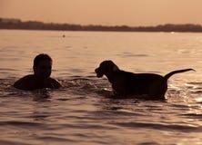 Abendsonnenuntergang: Junge mit Welpen in den Wellen Lizenzfreie Stockfotografie