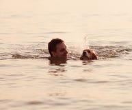 Abendsonnenuntergang: Junge mit Welpen in den Wellen Lizenzfreie Stockfotos