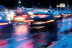 Abendstadtverkehr, der während des Regens fährt Unscharfe Bewegung Lizenzfreie Stockbilder