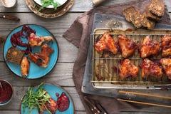 Abendtisch mit Hühnerflügeln in der Preiselbeersoße Lizenzfreies Stockbild