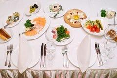 Abendtisch mit verschiedenen Tellern und leerem Tischbesteck Stockfotos