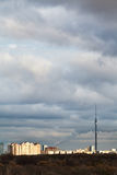 Abendwolken über Häusern und Fernsehturm Stockbilder