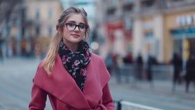 Abendzeit, das reizend Mädchen, das in die Stadt allein wandert, schaut in Richtung zur Kamera recht und gibt ein reizend Lächeln stock video