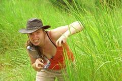 Abenteuer-Frau versteckt sich im Gras, das vortäuscht, ein Tier zu sein lizenzfreie stockfotos
