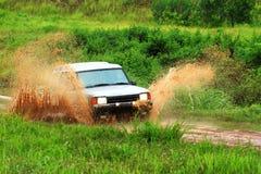 Abenteuerauto-Laufwerkpflüge durch das Wasser Stockbild