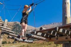 Abenteuerkletterseilpark - eine junge Frau geht entlang Klotz und Seile auf einer Höhe vor dem hintergrund der Berge und blauen s Stockbilder