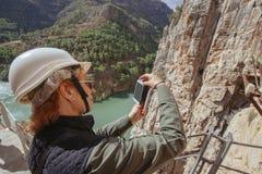 abenteuerliche Frau mit dem Sturzhelm, der ein Foto mit ihrem Telefon auf einer Klippe macht Stockbild