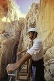 abenteuerlicher Mann mit dem Sturzhelm, der eine Klippe auf einem Berg schätzt Stockbilder