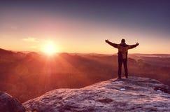 Abenteurer auf der Klippe und Blicke in den erstaunlichen sonnigen Tag awaiking lizenzfreies stockfoto