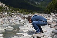 Abenteurer, der von einem Fluss trinkt Stockbild